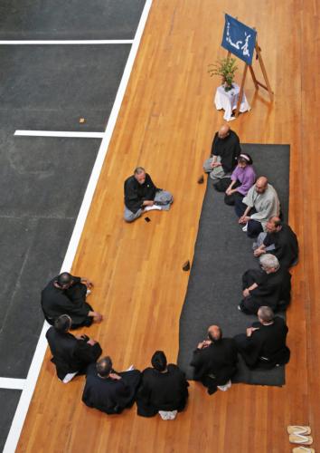 Grupo de practicantes de kyudo sentados en círculo escuchan enseñanzas del sensei