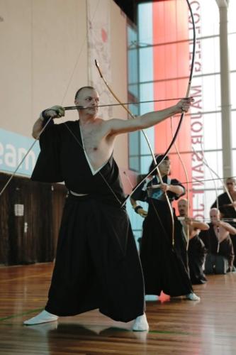 """Practicantes de kyudo en kimono, durante un sharei. En primer plano, practicante en posición de """"kai"""", a punto de disparar su flecha. Asociación Española de Kyudo"""