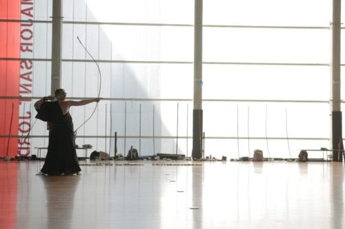 """Practicante de kyudo en un sharei, en postura """"kai"""", a punto de disparar la flecha."""