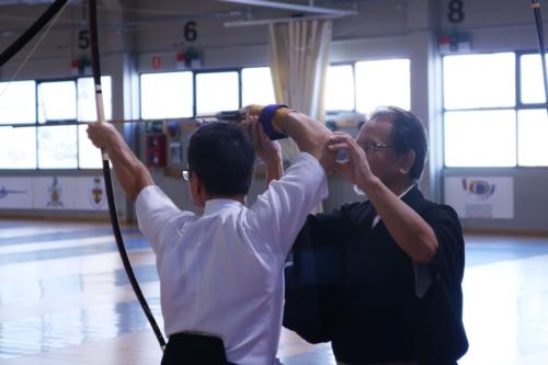 Sensei dando instrucciones a un practicante de kyudo mientras abre el arco.